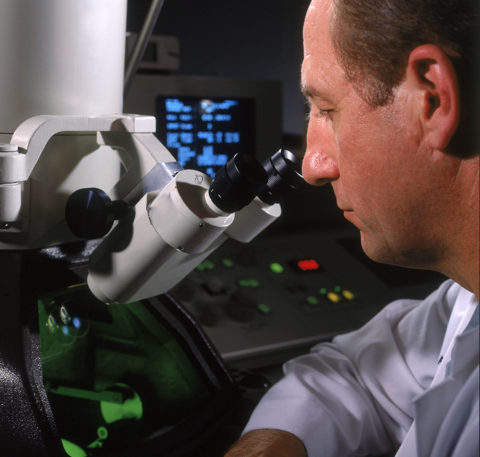 photo of surgeon with microscope in medical facility