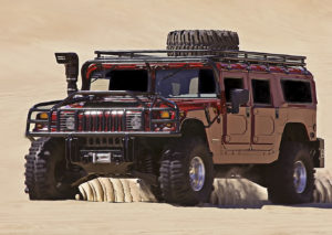 Hummer SUV driving off road on sand dunes