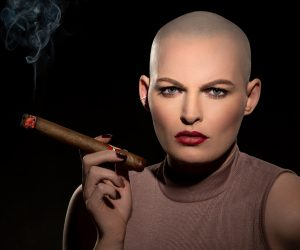 headshot of bald female model with cigar