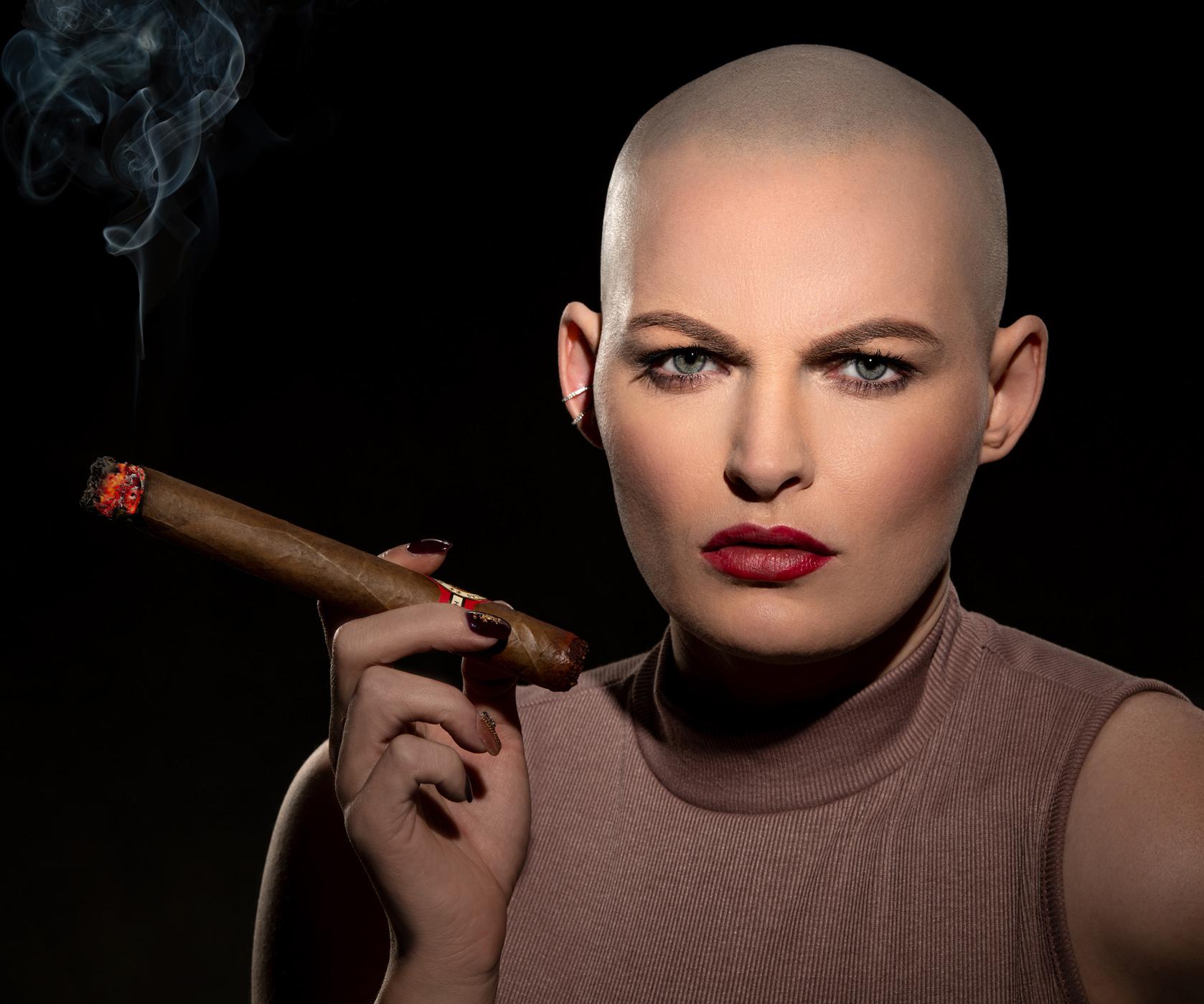 headshot of bald female model with cigar